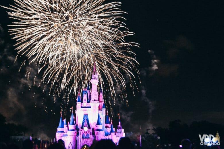 Foto do Wishes, o show de fogos, com o castelo da Cinderela iluminado em rosa. Todo mundo que viu sente saudades desse show!