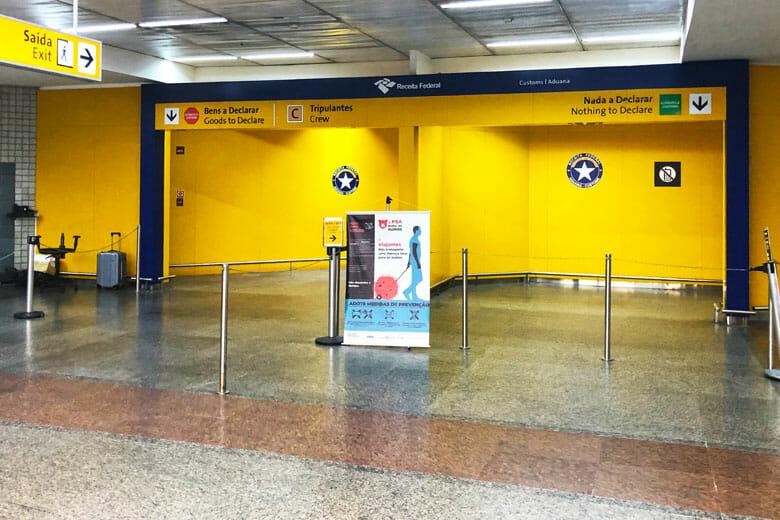 Foto da alfândega vazia no aeroporto de Guarulhos. As paredes são pintadas de amarelo e tem o símbolo da Polícia Federal