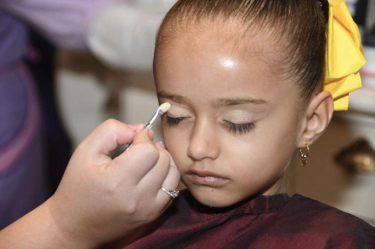 Foto da filha do leitor Fabiano com um laço amarelo no cabelo, sendo maquiada no Bibbidi Bobbidi Boutique