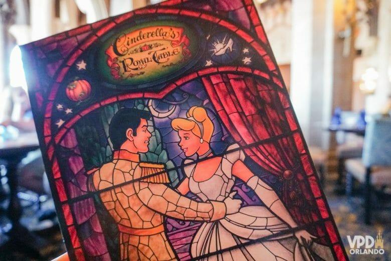 Foto do cardápio do Cinderella's Royal Table. O cardápio tem a imagem de um vitral, com a Cinderela e o príncipe dançando, debaixo do nome do restaurante.