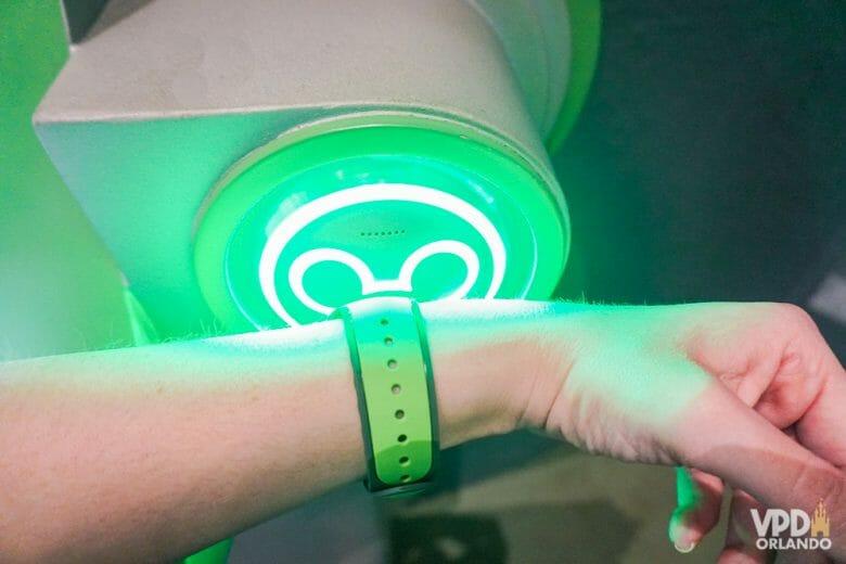 Foto de uma hóspede de um hotel da Disney escaneando a MagicBand verde na entrada de uma atração. A entrada tem um visor em forma de Mickey, que fica verde ao escanear a MagicBand.