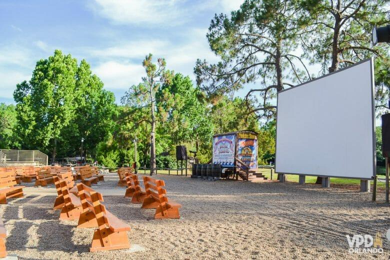 Foto do cinema a céu aberto no hotel Fort Wilderness. Há bancos para os visitantes sentarem e um telão em branco sobre a areia, com árvores em volta.
