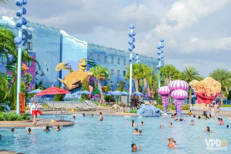 A foto mostra visitantes na piscina do hotel da Disney, o Art of Animation. A decoração é colorida, o prédio ao fundo é azul e a tartaruga do filme Procurando Nemo é parte da decoração.