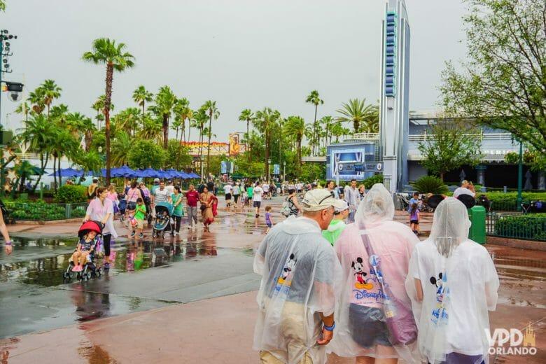 Foto de uma área aberta no parque em um dia nublado. Os visitantes estão com capas de chuva.