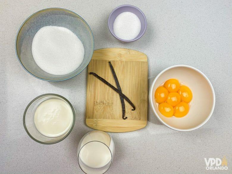 Foto dos ingredientes da receita: açúcar, ovos, fava de baunilha, leite e creme de leite fresco