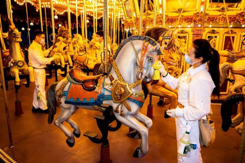 Foto de uma funcionária de máscara fazendo a limpeza do cavalo do carrossel da Disney de Hong Kong