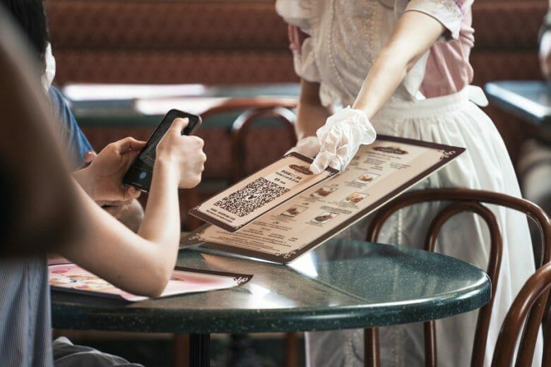 Foto de uma funcionária de luvas nas mãos entregando um cardápio a um visitante na Disney de Hong Kong