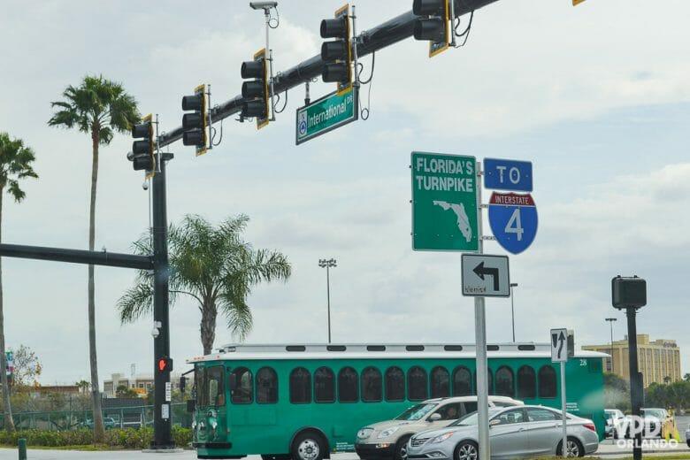 Imagem de uma rua em Orlando, com ônibus e carros parados no semáforo. As placas indicam o caminho para as rodovias.