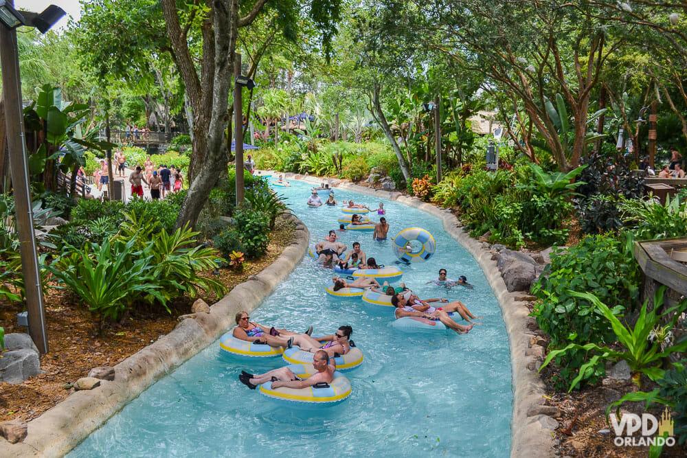 Imagem do rio de corredeira no parque aquático Typhoon Lagoon. Os visitantes estão flutuando no rio sobre boias, e há árvores ao redor.