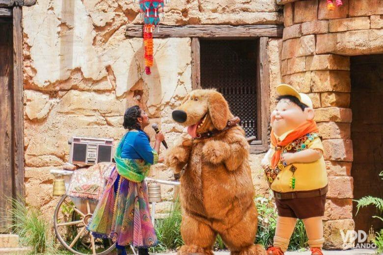Foto do palco durante o show do filme Up! no Animal Kingdom. A imagem mostra o cachorro Dug e o personagem Russell interagindo com a apresentadora.