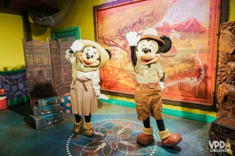 Foto do Mickey e da Minnie com roupa de safári, acenando para a foto, durante um encontro com visitantes.