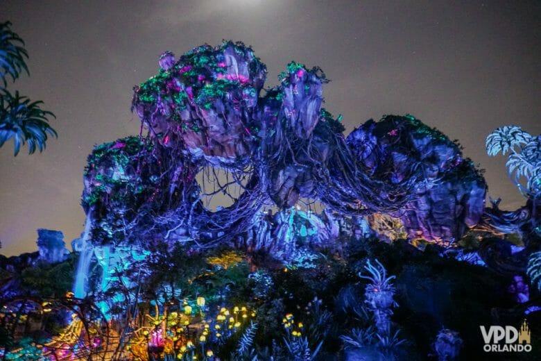 A área de Pandora no Animal Kingdom fica ainda mais incrível à noite! Foto das rochas na decoração de Pandora à noite, iluminadas em azul escuro com luzinhas coloridas mais abaixo
