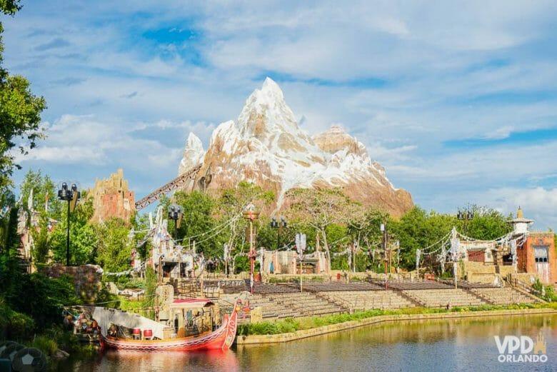 Foto da área da Ásia no Animal Kingdom, com a Everest ao fundo, o céu azul e parte do lago visível.