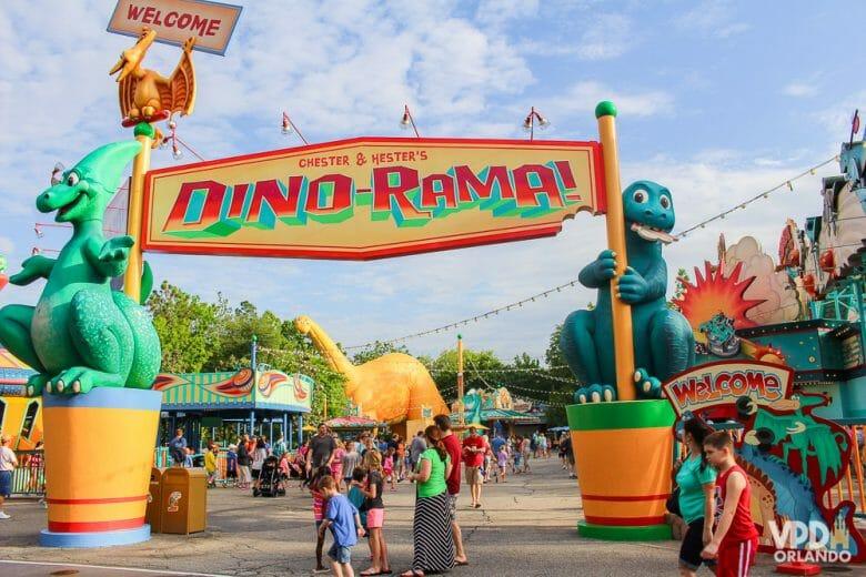 """Foto de uma placa que diz """"Dino-Rama"""", segurada por dois dinossauros, na área Dinoland U.S.A"""