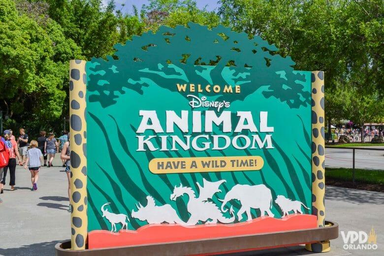 O Animal Kingdom merece um dia inteiro pra ele! Foto da entrada do parque, com uma placa de boas-vindas com o logo em um fundo verde.