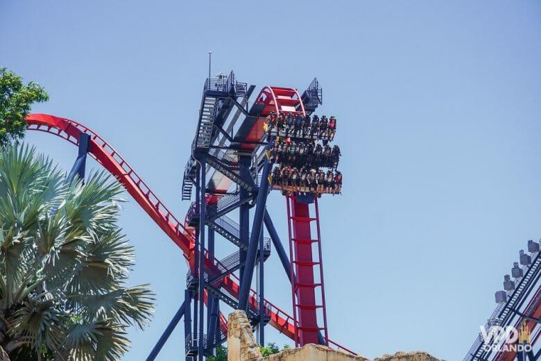 Sheikra: uma das montanhas russas mais famosas do Busch Gardens e com certeza imperdível pra quem gosta! Foto da montanha-russa Sheikra, do Busch Gardens. O carrinho está no alto de um looping, e é possível ver os trilhos curvados e o céu azul ao fundo.