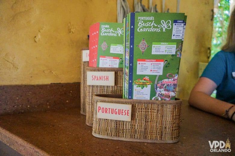 Mapas do parque Busch Gardens em uma cesta, com opção de idioma português e espanhol.