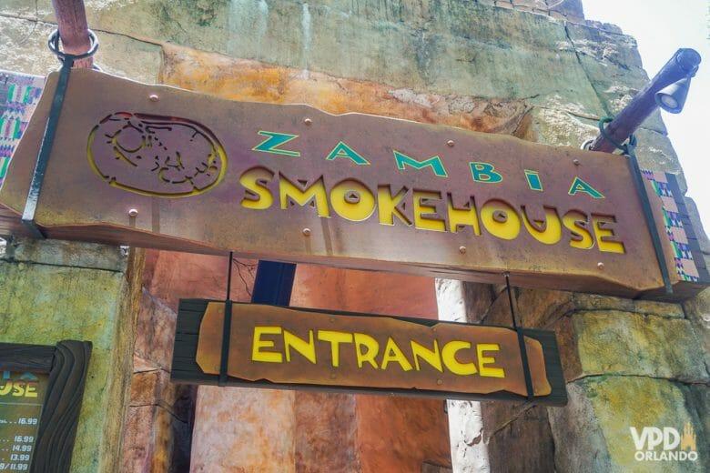 Opção gostosa de restaurante no Busch Gardens. Foto da placa na entrada do restaurante Zambia Smokehouse, em letras verde e amarelas sobre um fundo marrom