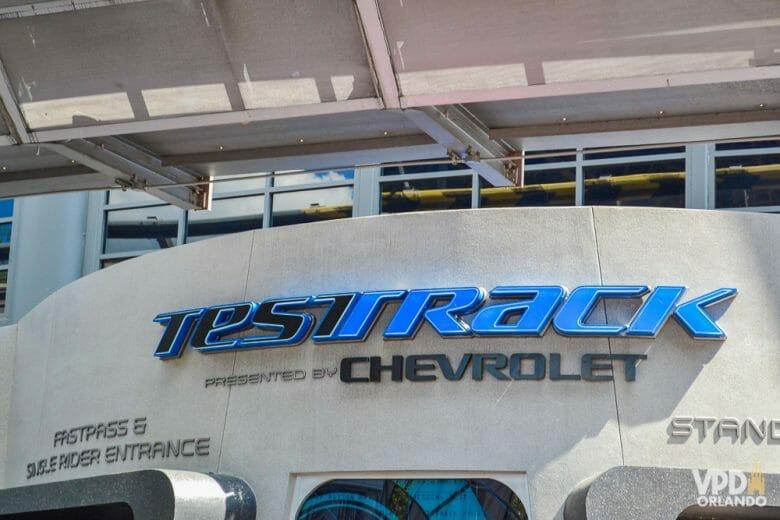 A Test Track tem a opção de fila single rider. Foto da entrada da Test Track no Epcot, com o título escrito em azul e preto.