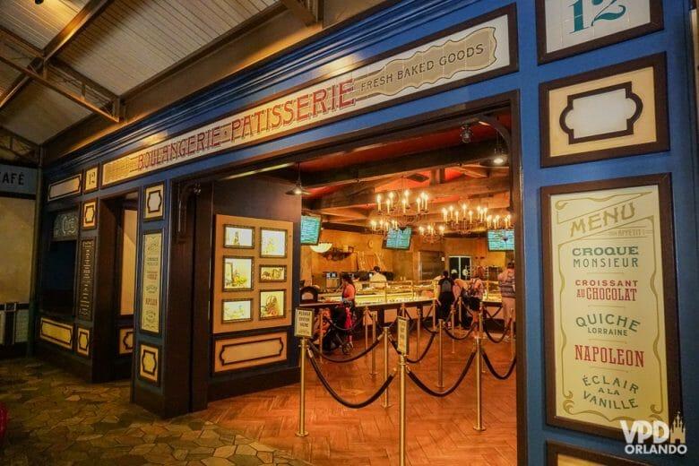 A Patisserie no fundo do pavilhão é cheia de opções gostosas. Foto da Patisserie no pavilhão da França do Epcot, com o menu de itens franceses na parede ao lado da porta.