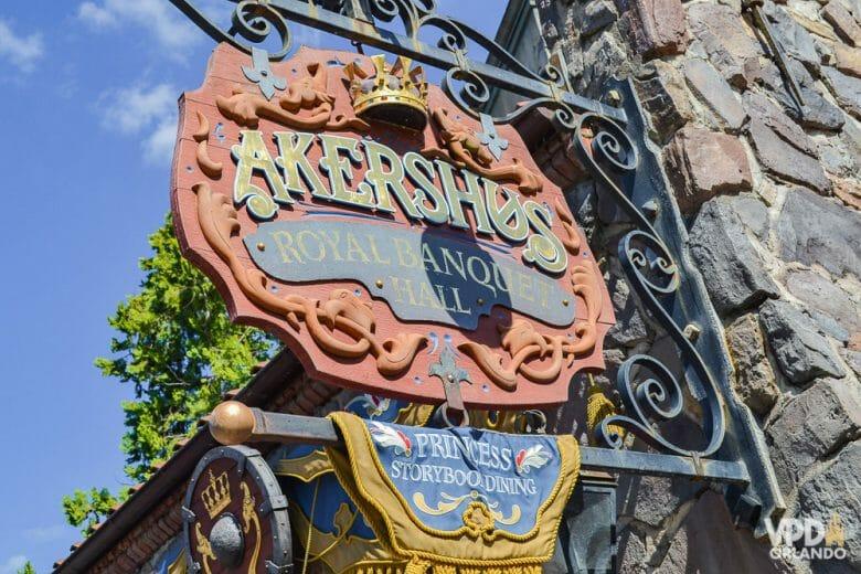 O Akershus é uma opção de refeição com as princesas no Epcot. Foto da placa na entrada do Akershus Royal Banquet Hall, com letras medievais e uma coroa sobre o título.