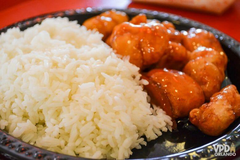 O frango empanado ao molho de laranja do pavilhão da China é um dos meus preferidos no Epcot! Foto de um prato com frango empanado e arroz