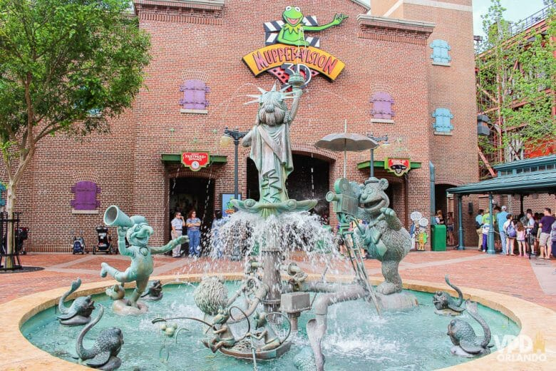Atração 3D dos Muppets, que tá precisando de uma atualização! Foto da fonte que fica em frente à atração dos Muppets no Hollywood Studios, que tem os personagens esculpidos em pedra em diferentes poses, com a Miss Piggy de Estátua da Liberdade ao centro.