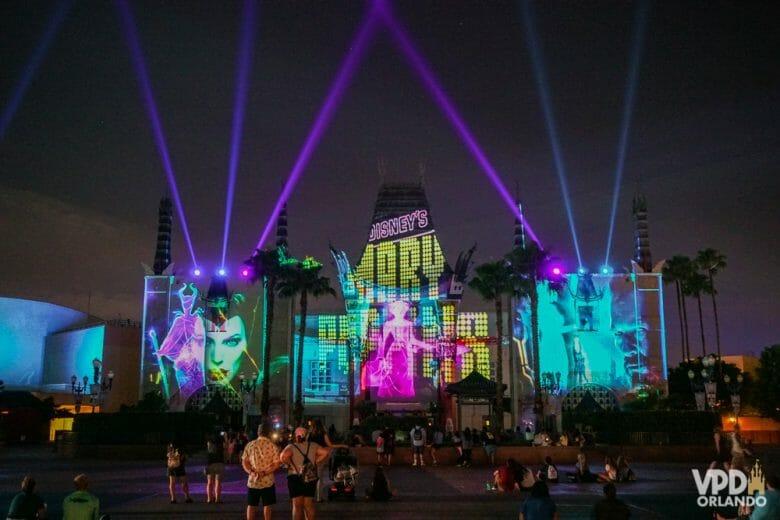 Show de projeções no teatro Chinês pra finalizar o dia! A foto mostra o Teatro Chinês do Hollywood Studios com projeções de personagens da Disney, como Malévola e Mary Poppins, e luzes que se lançam no céu.
