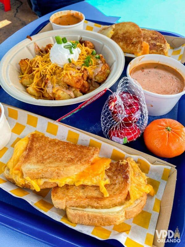 Esse pão com queijo e sopa de tomate é uma delícia. Foto do prato no Woody's Lunch Box do Hollywood Studios, que mostra um queijo quente com sopa de tomate e batatas com queijo.