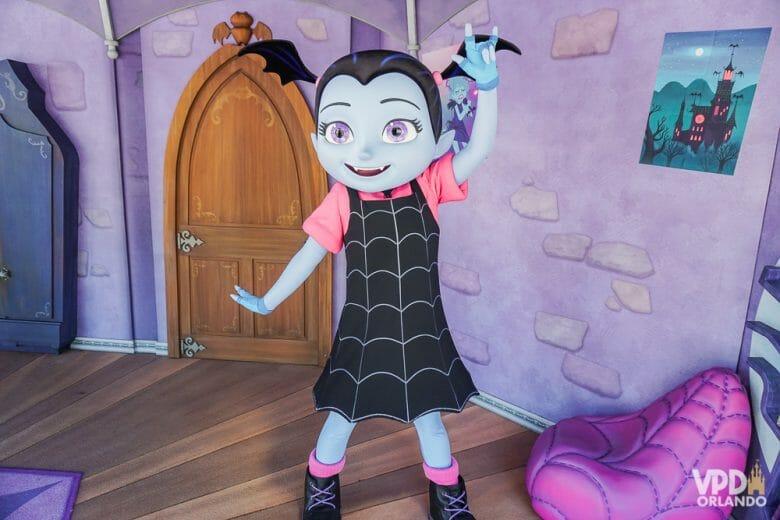 Os personagens de Disney Junior ficam ali encontrando os visitantes. Foto da personagem Vampirina, no Hollywood Studios, acenando para visitantes em uma casa com paredes roxas.