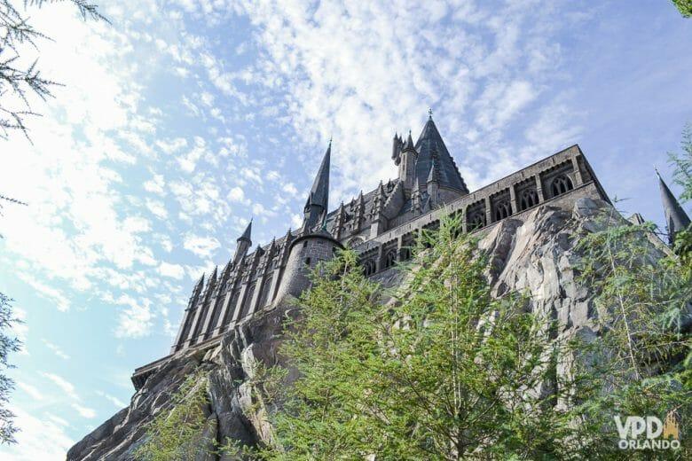 Foto do castelo de Hogwarts na Universal, com o céu azul ao fundo e árvores ao redor.