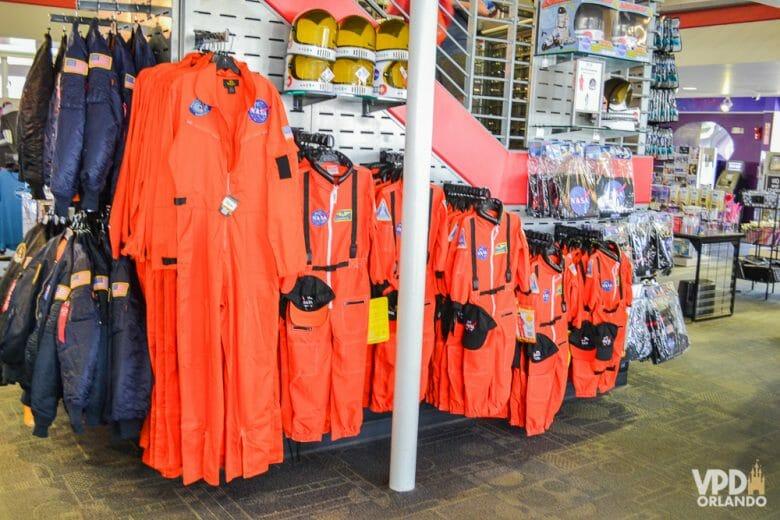 Há! Duvido que você não quer um macacão desses? Foto dos macacões de astronauta alaranjados à venda em uma loja