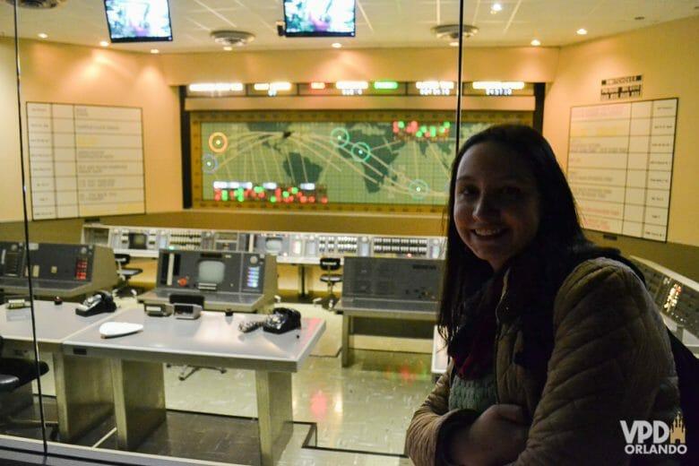 Foto da Renata ao lado de uma réplica da sala de controle da missão Mercury