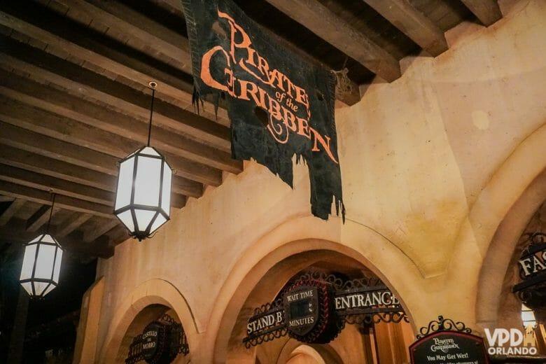 Foto da entrada da atração Pirates of the Caribbean no Magic Kingdom. A placa da atração imita uma bandeira pirata esfarrapada.