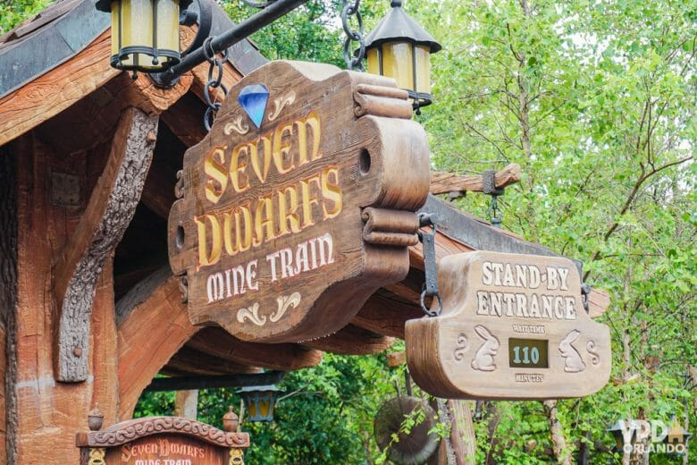 "Foto da entrada da Seven Dwarfs Mine Train no Magic Kingdom. As placas de madeira exibem o nome da atração e ""stand-by entrance"" com o tempo de espera abaixo"