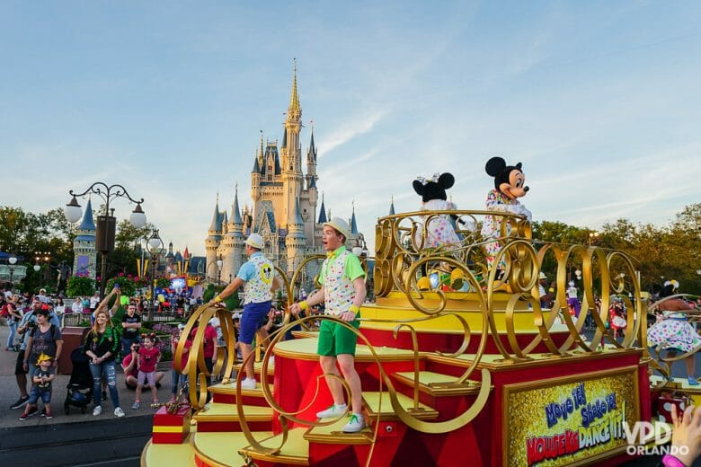 Foto do carro durante uma das paradas do Magic Kingdom, com o Mickey, a Minnie e dois animadores, com o castelo visível ao fundo.