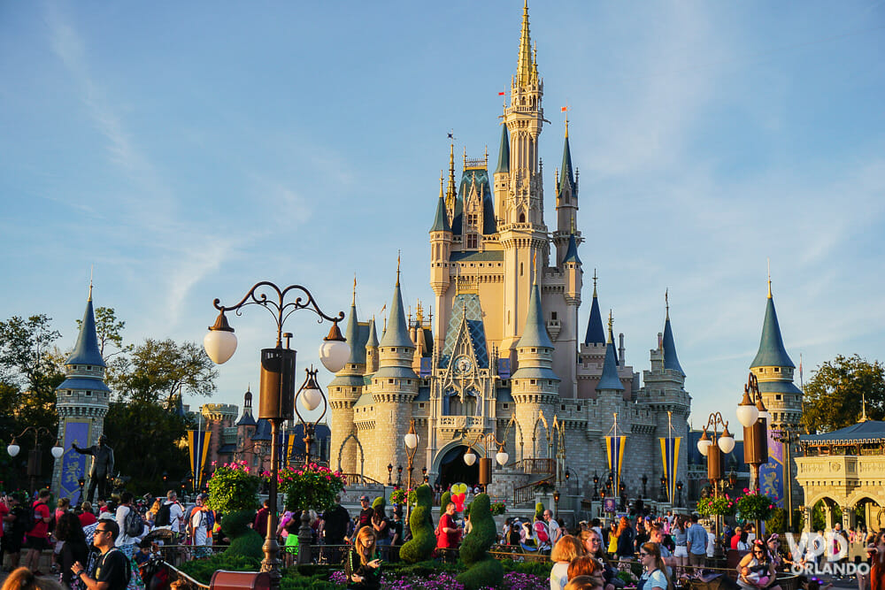 Imagem do Magic Kingdom durante o dia, com muitos visitantes e o Castelo da Cinderela ao fundo.