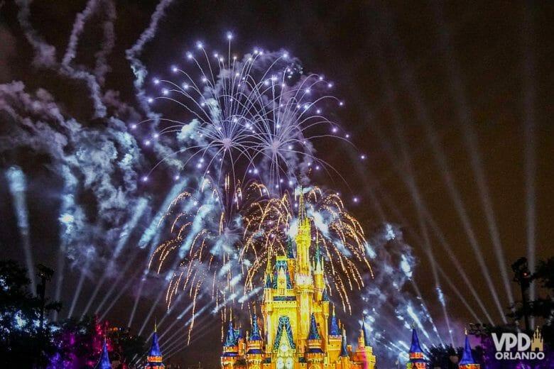 Foto do castelo da Cinderela no Magic Kingdom, iluminado em amarelo com os fogos de artifício no céu noturno.