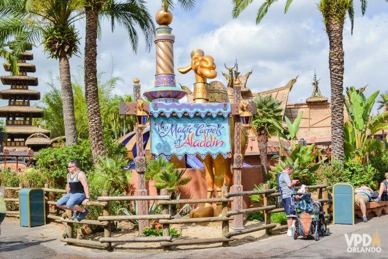 """Foto da entrada da atração de Aladdin no Magic Kingdom. A placa é azul-clara e diz """"The Magic Carpets of Aladdin"""" na mesma fonte usada para o filme."""