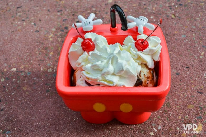 Foto do sundae do Mickey vendido no Magic Kingdom, num recipiente vermelho, com uma cobertura de chantilly e duas cerejas.