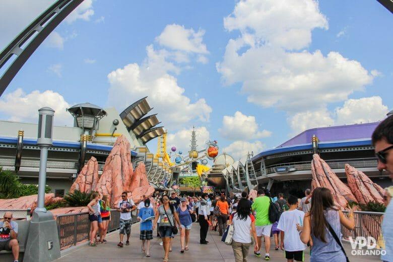 Foto da entrada da Tomorrowland no Magic Kingdom durante o dia, com as decorações espaciais visíveis ao fundo e visitantes indo em sua direção