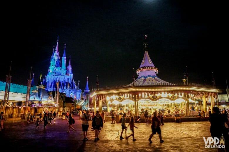 Foto da Fantasyland do Magic Kingdom à noite, com o carrossel iluminado e o castelo da Cinderela também iluminado ao fundo