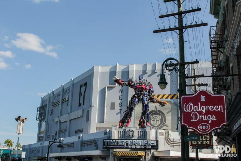 Foto na frente do simulador de Transformers na Universal Studios, com um dos robôs do filme em tamanho gigante acima da placa.