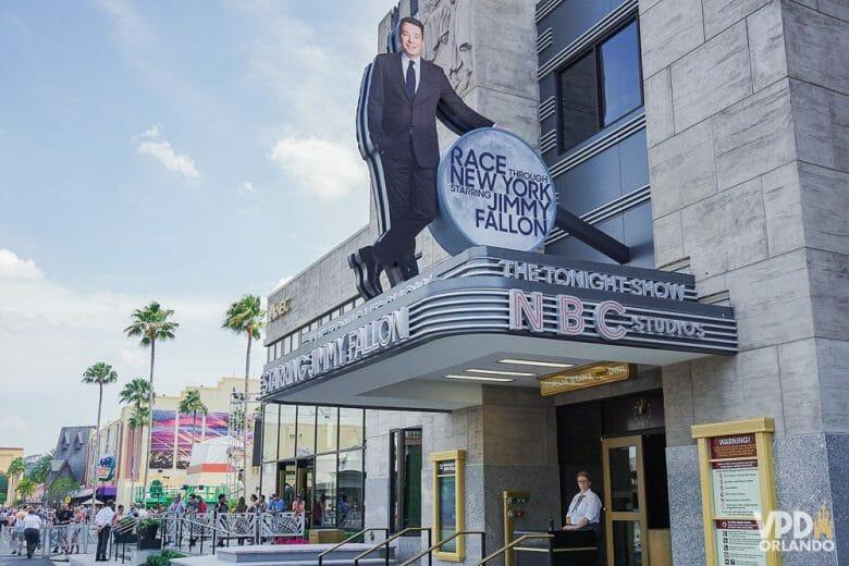 A atração do Jimmy Fallon na Universal Studios oferece fila virtual! Foto da entrada da atração Race Through New York Starring Jimmy Fallon, mostrando o apresentador na placa. A entrada do simulador se assemelha a um teatro clássico