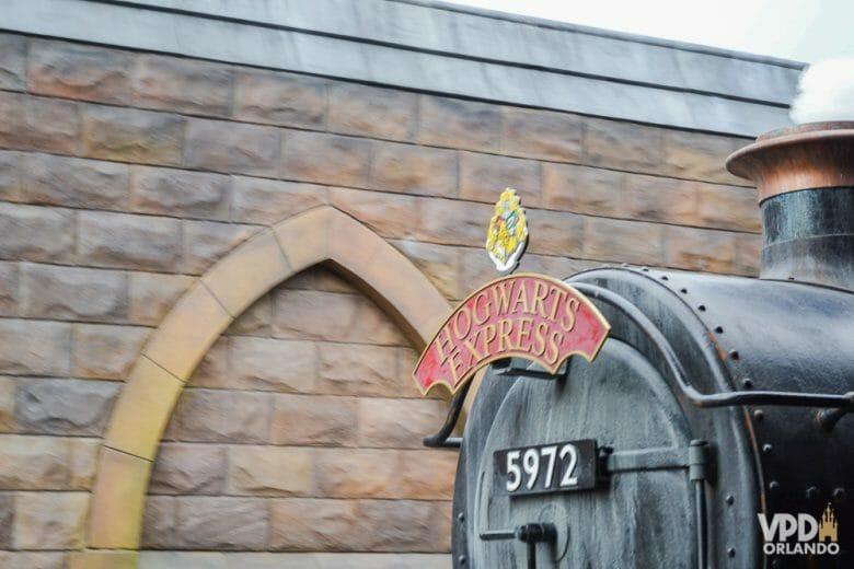 Foto do Expresso de Hogwarts da Universal, chegando à estação. Apenas sua frente é visível, assim como a parede de tijolos atrás.
