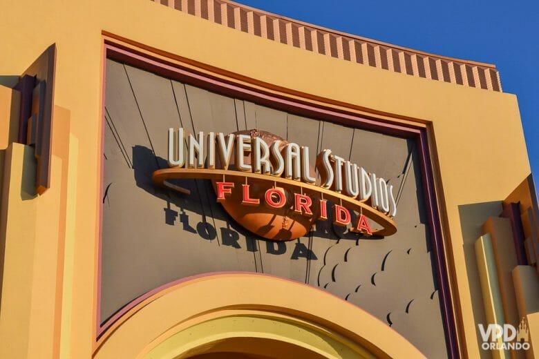Foto do portal do parque Universal Studios Florida, que mostra a placa com o nome do parque escrito em branco e laranja. O portal é pintado em bege e laranja-claro e o céu ao fundo está bem azul.