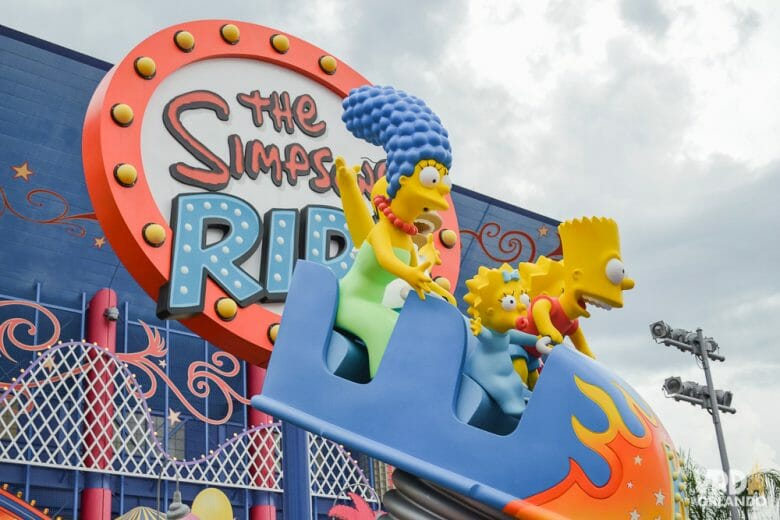 Foto da entrada a atração dos Simpsons na Universal Studios, com um carrinho com os personagens na frente da placa.