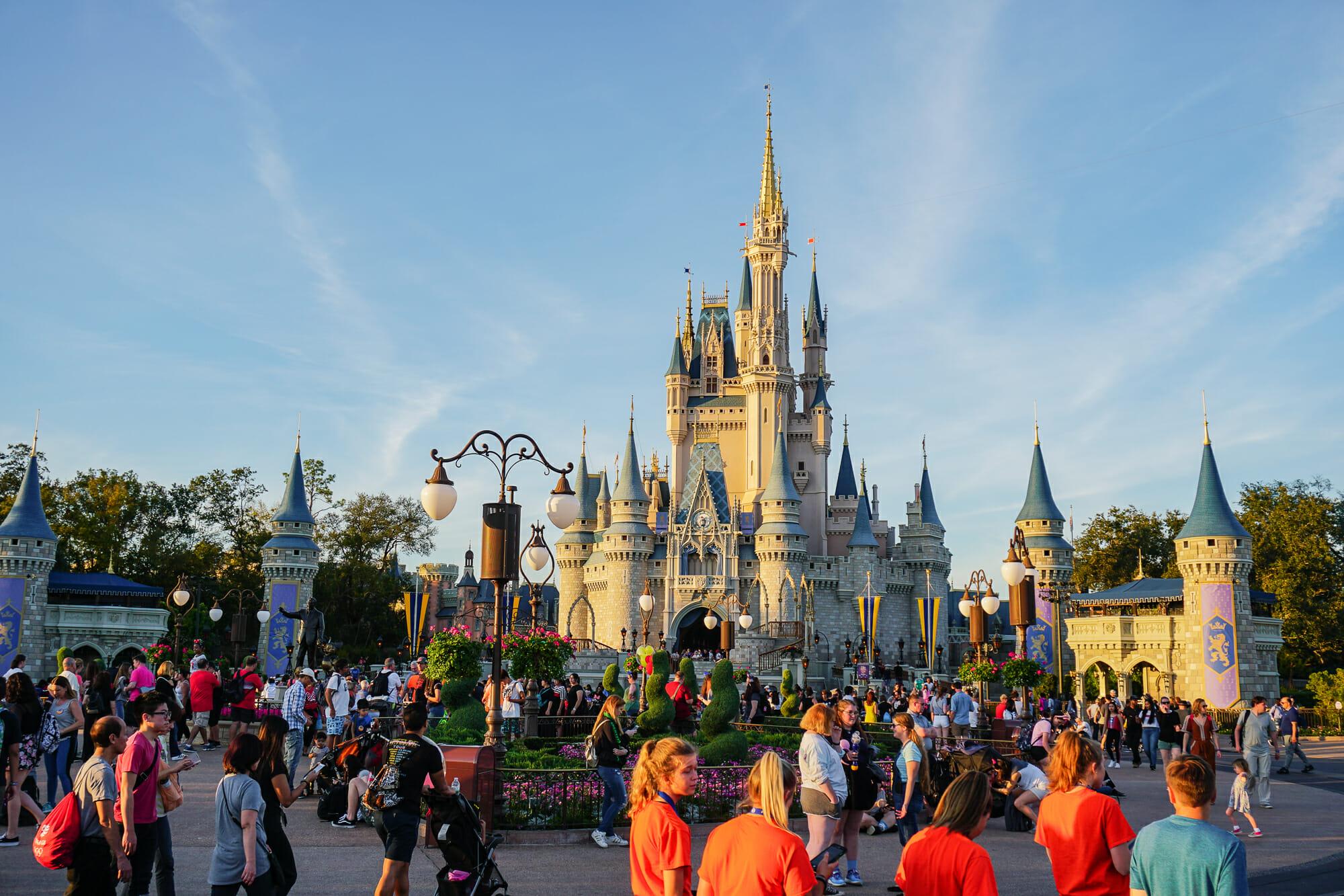 Foto do castelo da Cinderela do Magic Kingdom em um dia de céu azul, com muitos visitantes circulando pelo parque.