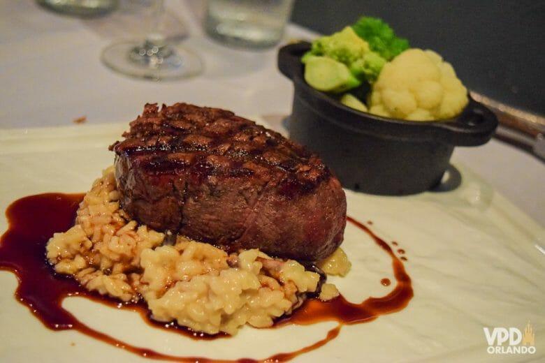 O Market to Table é um dos melhores restaurantes da região de Orlando. Foto do prato no Market to Table, com carne, risotto e legumes ao fundo.