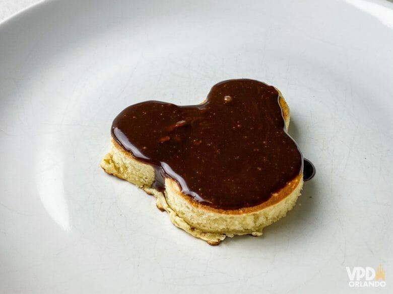 Pra fazer essa versão do Mickey, é só usar um cortador de biscoito ;) Foto de um prato com uma panqueca em formato de Mickey, coberta de chocolate